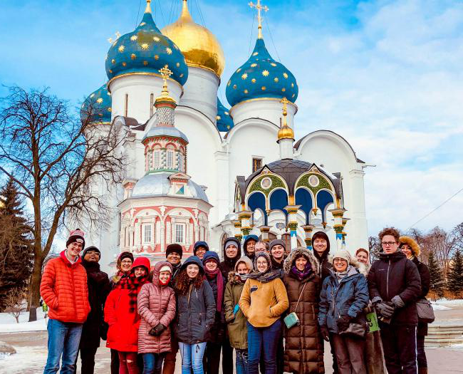 Students, faculty and staff in Russia stand near Russian Church