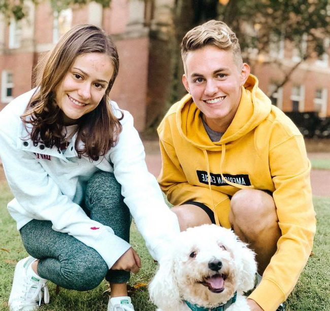 two student pose for picture with cute dog