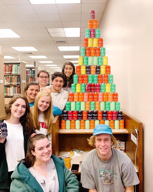 students stand proud next to their bubly can tower