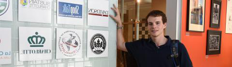 Student at his fellowship leans on glass wall with company logos