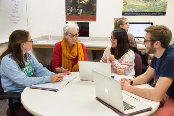 Prof. Munger sits at a round table with three students in her lab