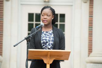 Jocelyn Kennedy '17 stands at podium in front of Chambers for the Law School Induction Ceremony