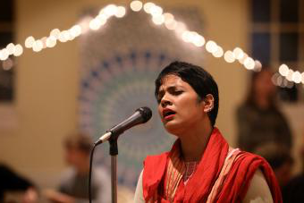 Singer at Diwali sings into microphone with eyes closed