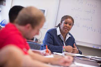 Professor Brenda Flanagan sits with students in class and gives lecture while students take notes