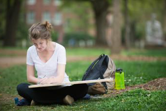 Student sits on grass with oversized drawing pad while drawing her campus surroundings