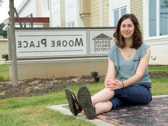 Elizabeth Welliver '16 sits on pavement next to the Moore Place community organization sign