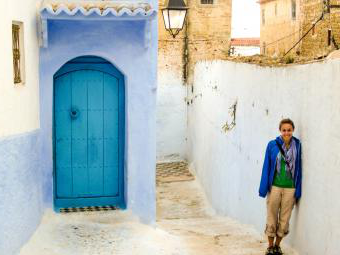 Student stands against white painted outdoor wall near a bright blue door in the streets of Morocco