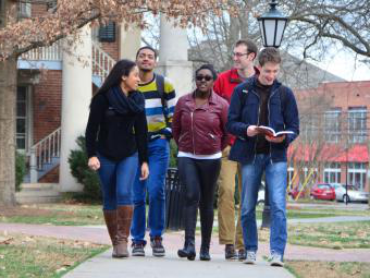 Group of students walk on edge of campus