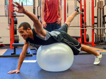 Student works out on an exercise ball in the Doe Weight Room