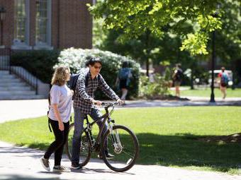 Students talk with one on bike