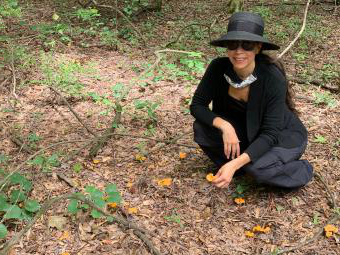Prof. Courtney Lewis kneeling with chanterelles