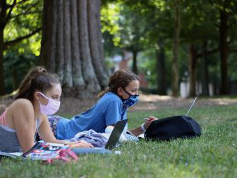Two students with masks on the lawn on computers
